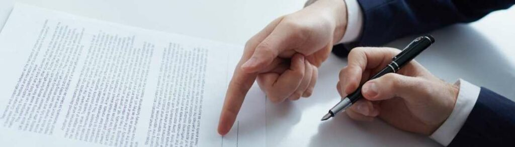 imagem de maos masculinas assinando um documento para ilustrar conteudo sobre vinculo de fiducia