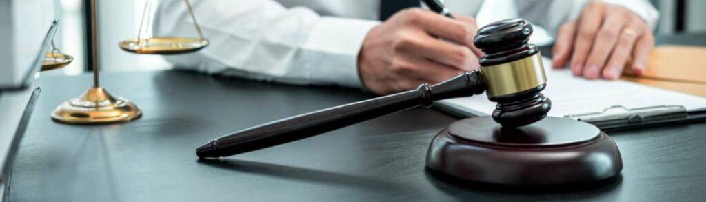 imagem de maos masculinas ao lado do martelo de juiz para ilustrar conteudo sobre o poder de direcao do empregador