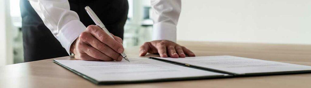 imagem das maos de um homem assinando um documento a caneta para ilustrar conteudo sobre contrato de trabalho