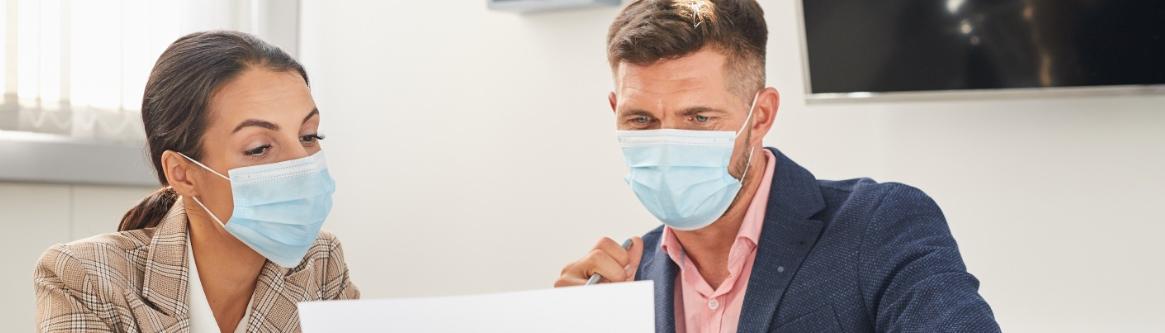 imagem com duas pessoas conversando, vestindo mascaras devido a pandemia, para ilustrar conteudo sobre recrutamento e selecao a distancia