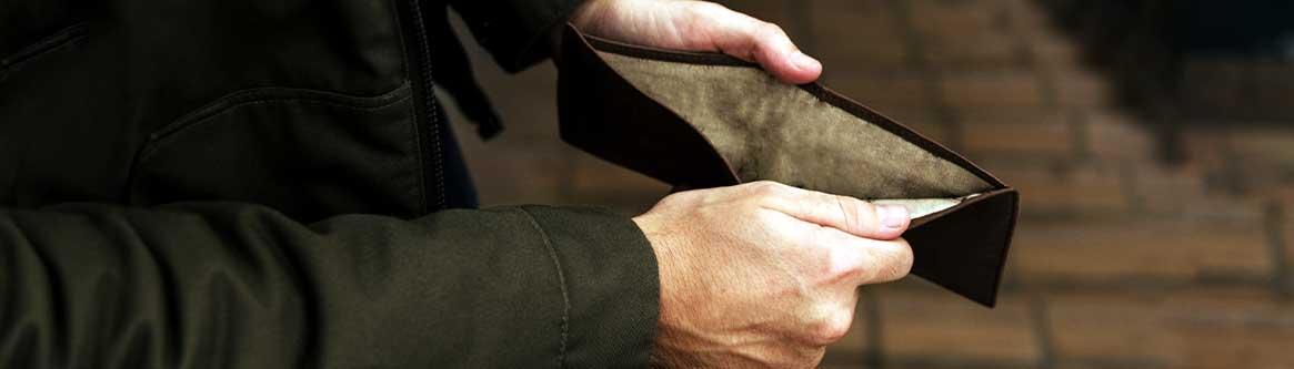 imagem de homem segurando uma carteira vazia para ilustrar conteudo sobre atrasou o salario